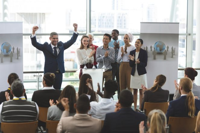 businessman-standing-with-arms-up-to-victory-at-podium-with-colleagues-at-business-seminar-in-office.jpg
